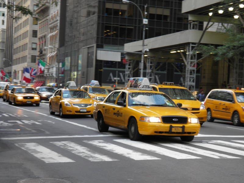 Die berühmten gelben Taxis, die in NYC an einem schönen Tag hetzen lizenzfreies stockfoto