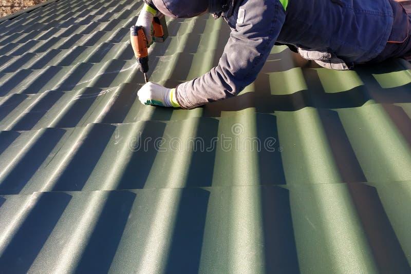 Die Berufsarbeitskraft arbeitet an Installation eines Dachs eines Dachs durch Blätter einer Metallfliese und bohrt eine Schraube  lizenzfreies stockbild