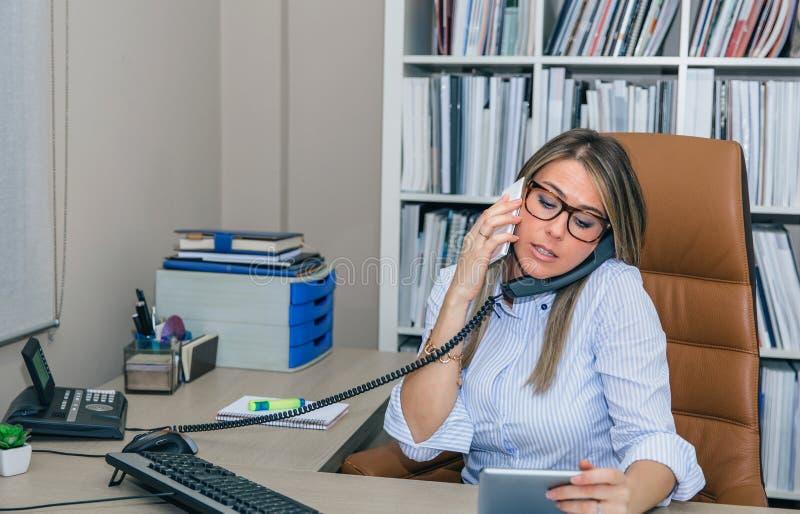 Die beschäftigte Geschäftsfrau, die mit Zelle sprechen und das Festnetz rufen im Büro an lizenzfreies stockfoto