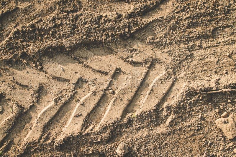 Die Beschaffenheit der Braunerde der Sandstraße mit Spuren der Reifenschritte der Autoreifen des Traktors Der Hintergrund lizenzfreie stockfotografie