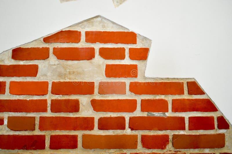 Die Beschaffenheit der konkreten alten zerschlagenen Wand des roten Backsteins des weißen Steins mit Sprüngen und exfoliated Gips lizenzfreies stockfoto
