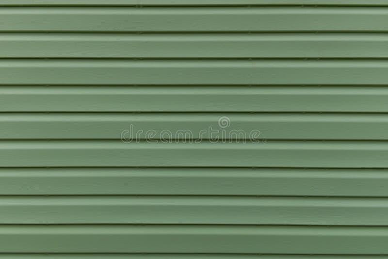 Die Beschaffenheit des grünen Brettes des Äußeren der HausSeitenkonsole Parallele abstrakte Streifen zeichnen lizenzfreie stockfotografie