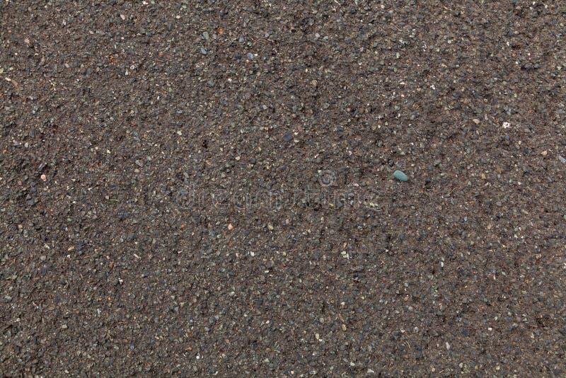 Die Beschaffenheit des grauen dunklen Sandes, der Hintergrund lizenzfreie stockfotos