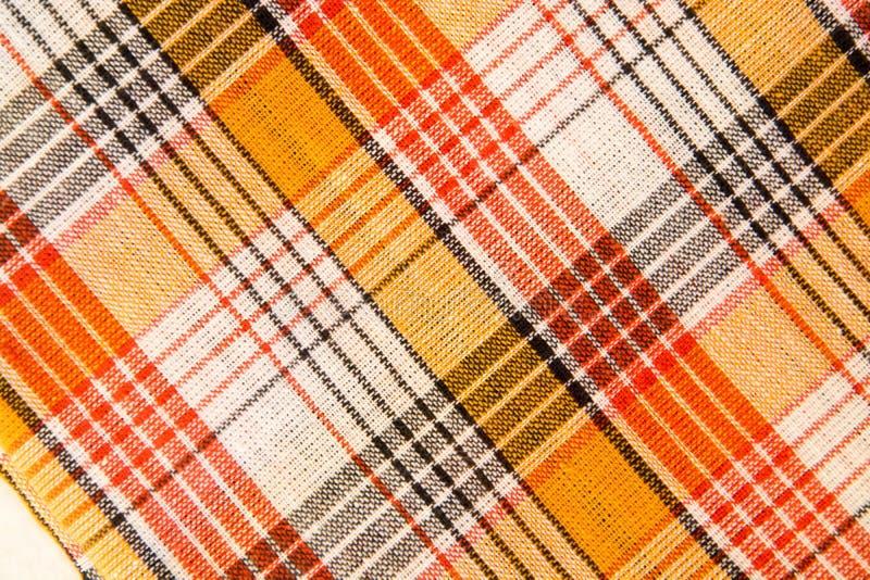 Die Beschaffenheit des weißen karierten, orange, roten, schwarzen Baumwollgewebees lizenzfreie stockfotos