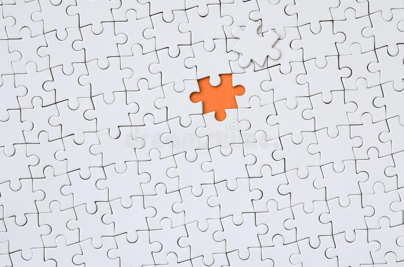 Die Beschaffenheit eines weißen Puzzlen in einem zusammengebauten Zustand mit einem Verfehlungselement, das einen orange Raum bil stockbild