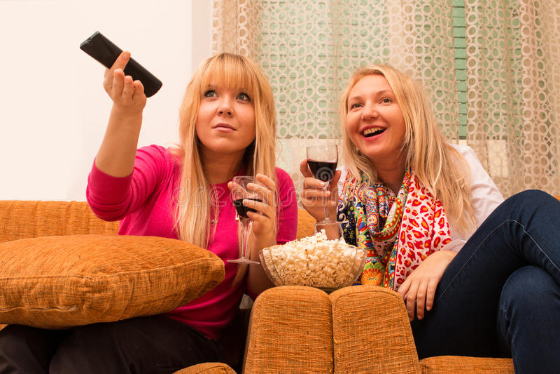 Die besten Freunde zu Hause, die fernsehen und Weinretrostil trinken, filterten Bild stockbilder
