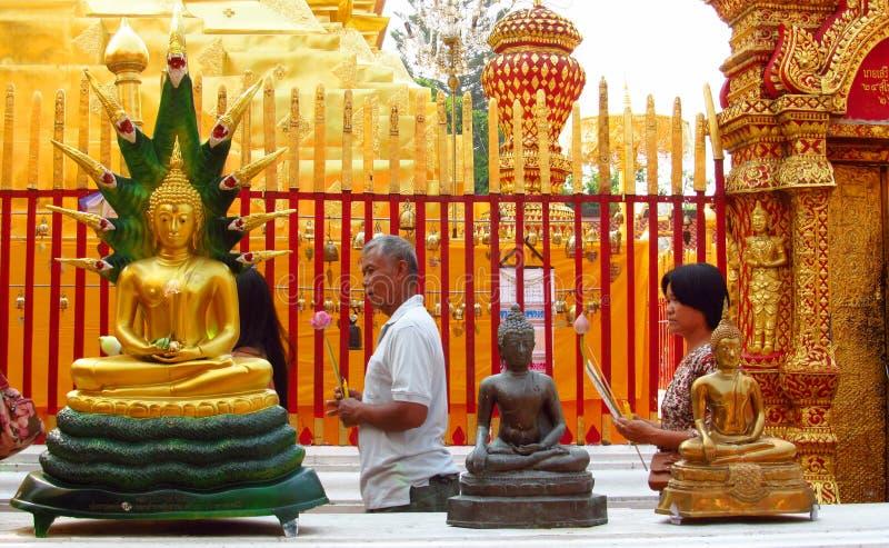 Die betenden Leute toGolden Buddha-Statue im buddhistischen Tempel stockfoto