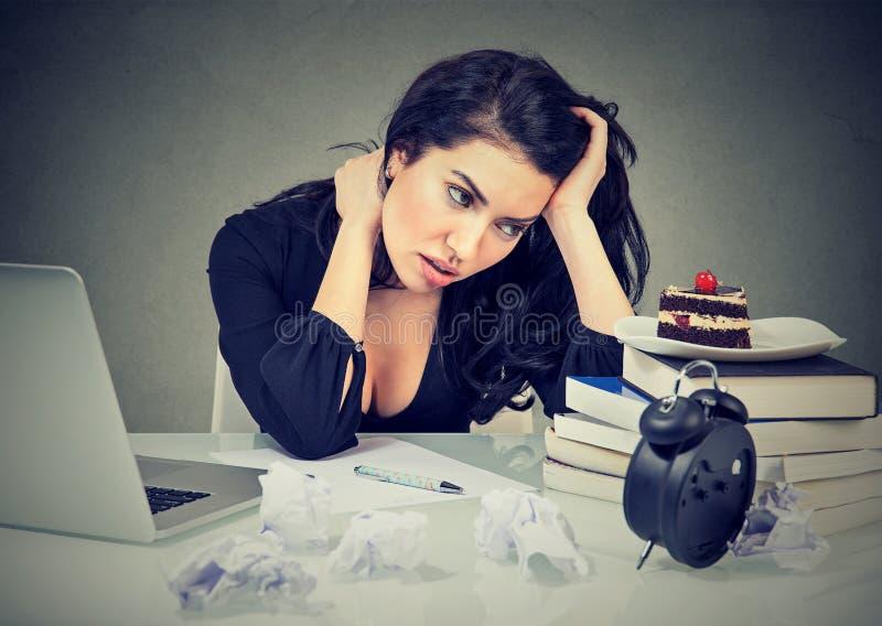 Die betonte Frau, die am Schreibtisch in ihrem Büro sitzt, überbelastete sehnenden süßen Kuchen lizenzfreies stockbild