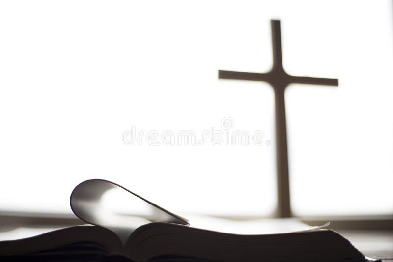 Die Bibel auf dem Hintergrund des Kreuzes und des belebenden Lichtes stockbild