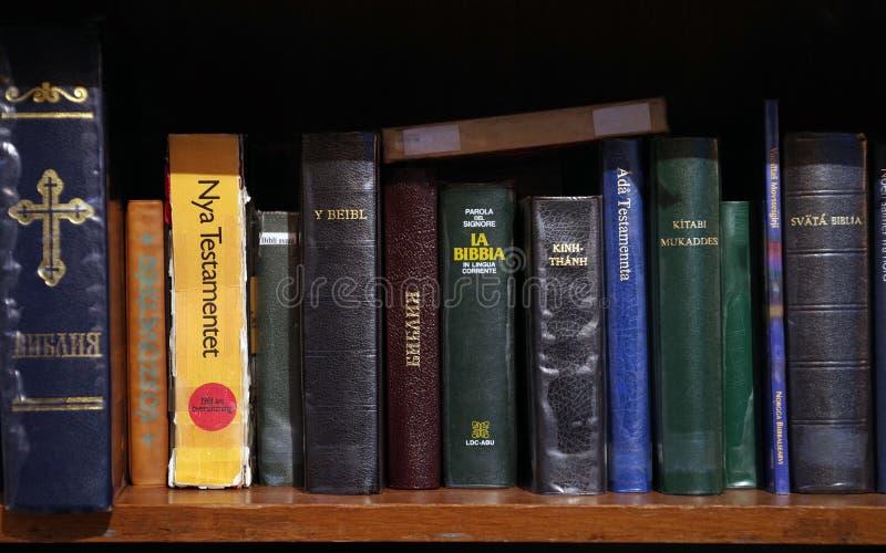 Die Bibeln in den verschiedenen Sprachen der Welt ist auf dem Bücherregal stockbilder