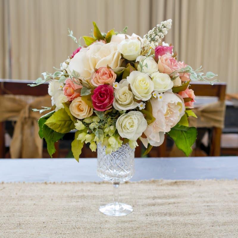 Die Blütenrose, die auf den Schreibtisch speisen gesetzt wird herein, Raum stockbild