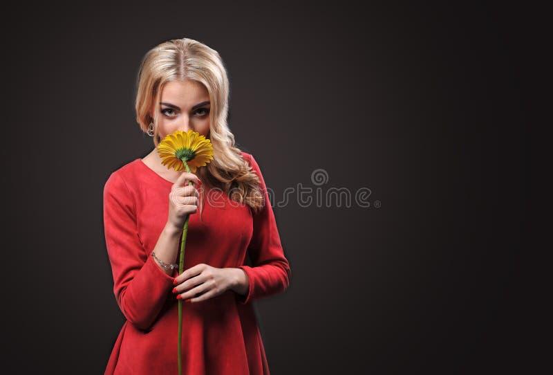 Die blonde Frau des jungen Mädchens auf einem schwarzen Hintergrund mit einer Blumenstraußniederlassung von gelben Chrysanthemen  lizenzfreie stockbilder