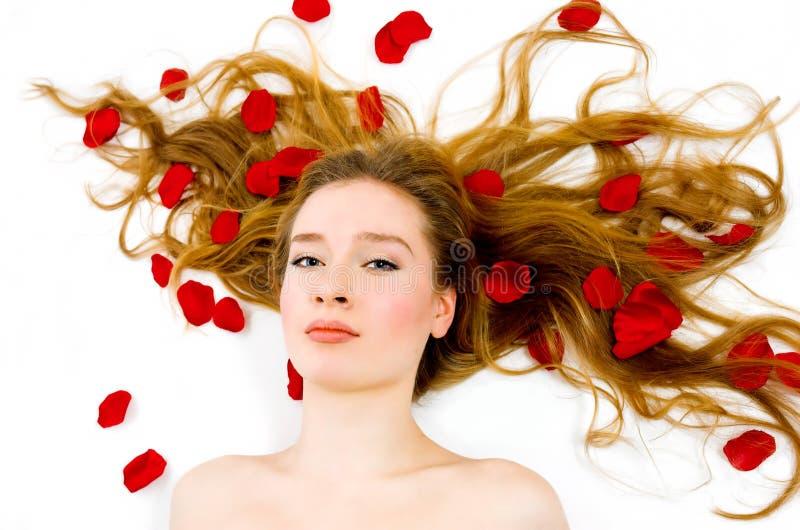 Die Blondine in den rosafarbenen Blumenblättern lizenzfreies stockbild