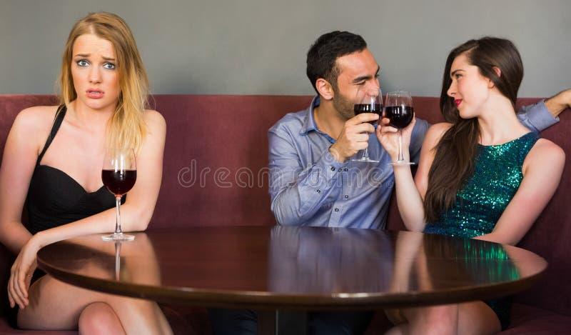 Die Blondine, die als zwei Leute eifersüchtig sich fühlen, flirten stockfotografie