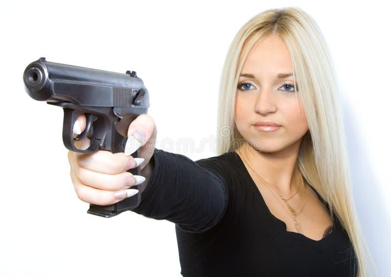 Die Blondine mit einer Pistole stockfotografie