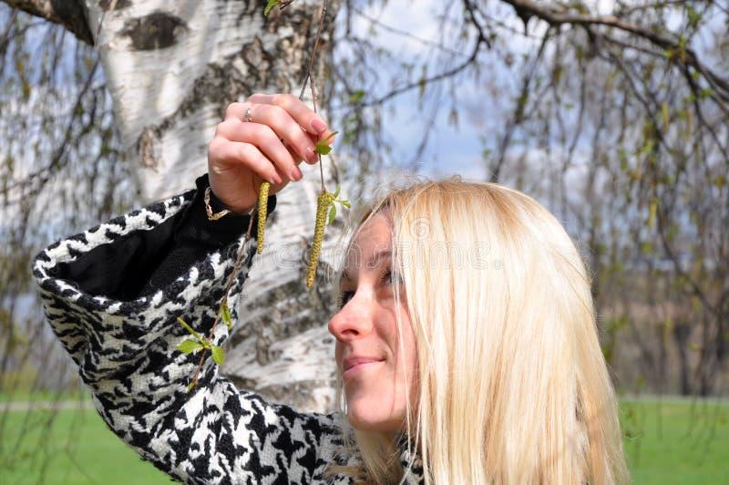 Die Blondine studiert Birkenohrringe lizenzfreies stockfoto