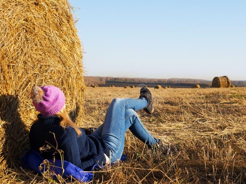 Die Blondinenlügen und -reste auf dem Herbstgebiet an einem sonnigen Tag stockfotos