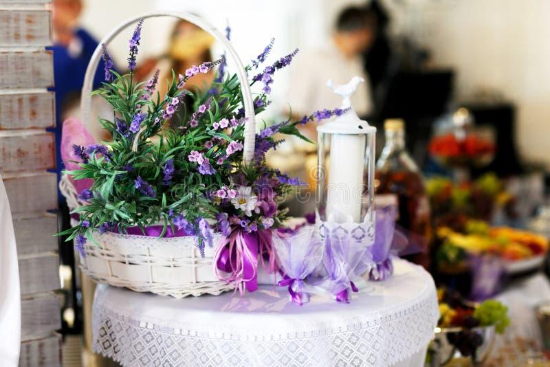 Die Bonbons, die in Tulle-Taschen verpackt werden, liegen hinter einem Korb mit violettem Fluss stockfotografie