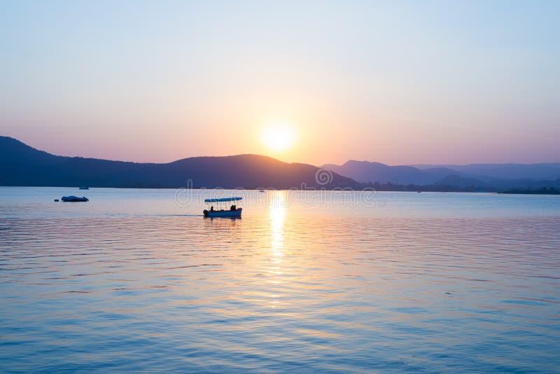 Die Boote, die auf See Pichola mit buntem Sonnenuntergang schwimmen, schwemmten auf Wasser beyong die Hügel von neuem inflationis stockbild