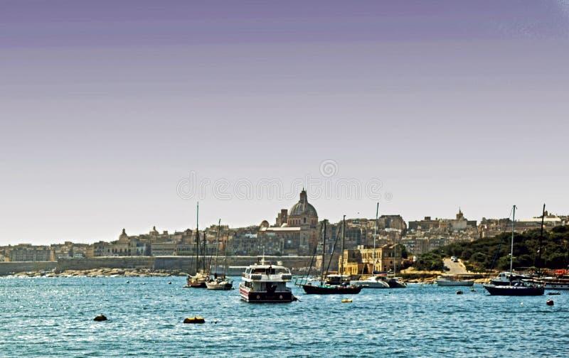 Die Boote, die in einem maltesischen Hafen festgemacht werden, dort sind Häuser, Gebäude und eine Kirche im Hintergrund lizenzfreies stockfoto