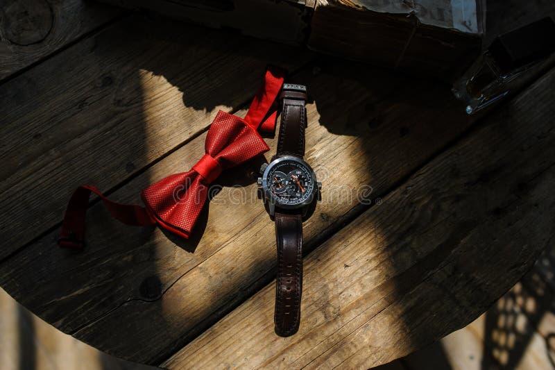 Die Bräutigam ` s Uhr und das rote bowtie stockfotos