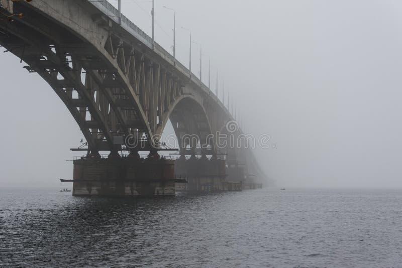 Die Brücke über dem Fluss im Nebel Ansicht von unterhalb der Bogenbrücke zum Fluss stockfotos