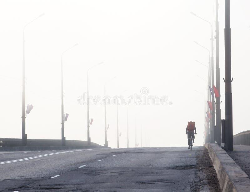 Die Brücke im Nebel über dem Volkhov-Fluss in Veliky Novgoro lizenzfreie stockbilder