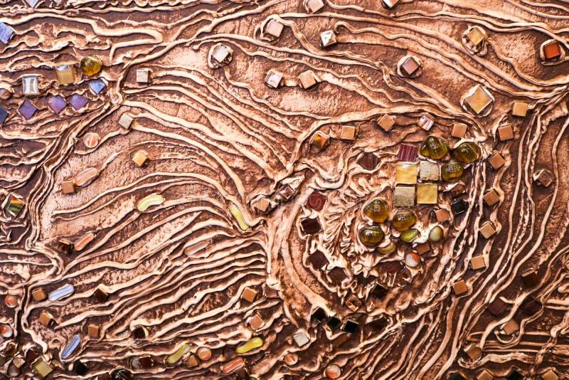 Die braune Beschaffenheit der Betonmauer wird vom dekorativen Gips mit dem Zusatz von mehrfarbigen Edelsteinen, von Glasquadraten stockbilder