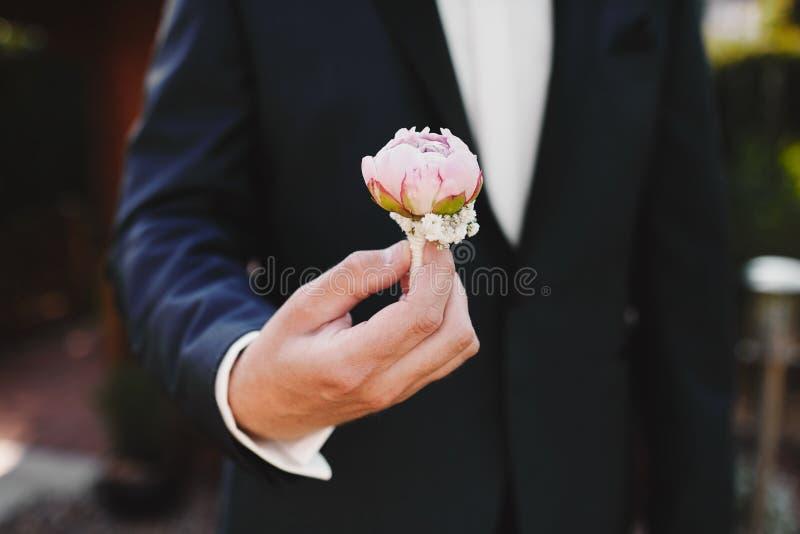 Die Braut, die in der Hand Nahaufnahme die Knopflochblumen des Bräutigams mit weißen Rosen halten, und Grün und Grün lizenzfreie stockfotografie