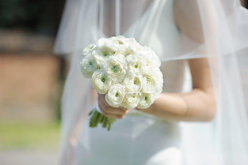 Die Braut, die weiße Hochzeit anhält, blüht Blumenstrauß stockbilder