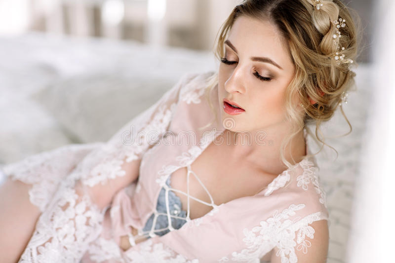 Die Braut in einem Bademantel zum Schlafzimmerfenster morgens lizenzfreie stockbilder
