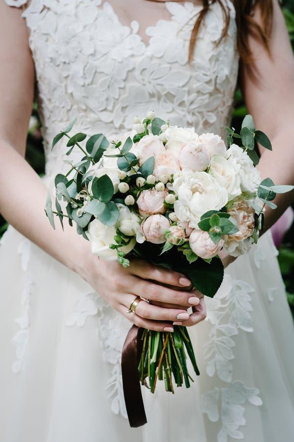 Die Braut, die einen schönen Hochzeitsblumenstrauß von Pastell, rosa, Pfingstrosen hält, Rosen blüht, Grün lizenzfreie stockfotografie