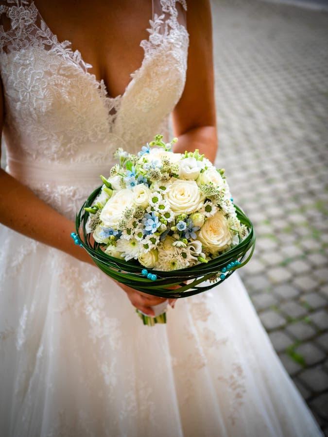 Die Braut hält den Blumenstrauß mit weißen Rosen und kleinen blauen Blumen lizenzfreie stockfotografie