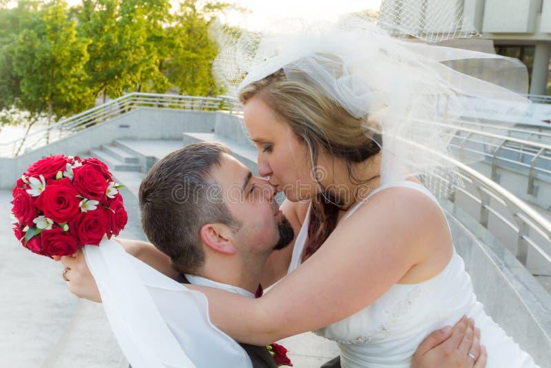 Die Braut küßt den Bräutigam stockfotos