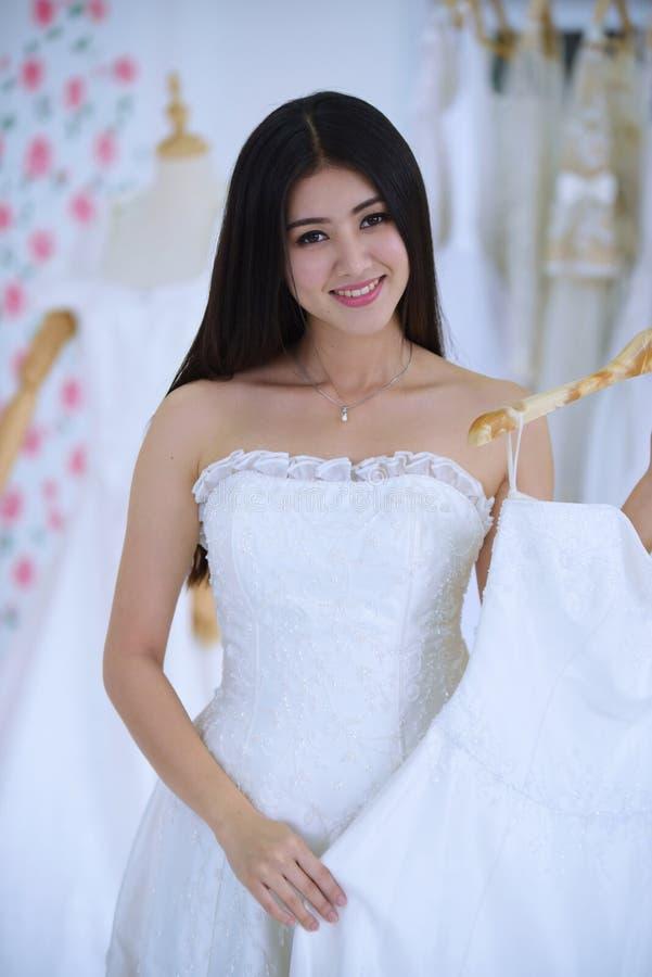Die Braut kam, die Vorbereitung des Brautkleides zu messen stockbild