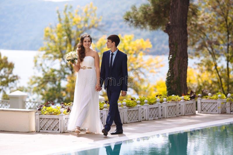 Die Braut mit dem langen dunklen Haar hält einen Hochzeitsblumenstrauß und lächelt glücklich, geht durch die Hand mit ihrem Ehema lizenzfreie stockbilder