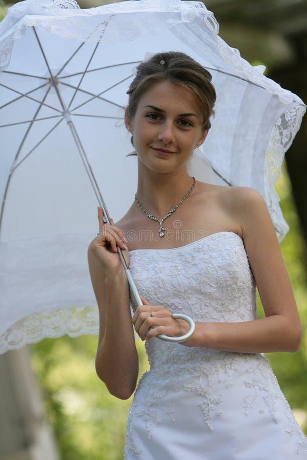 Die Braut mit einem Regenschirm stockfotografie
