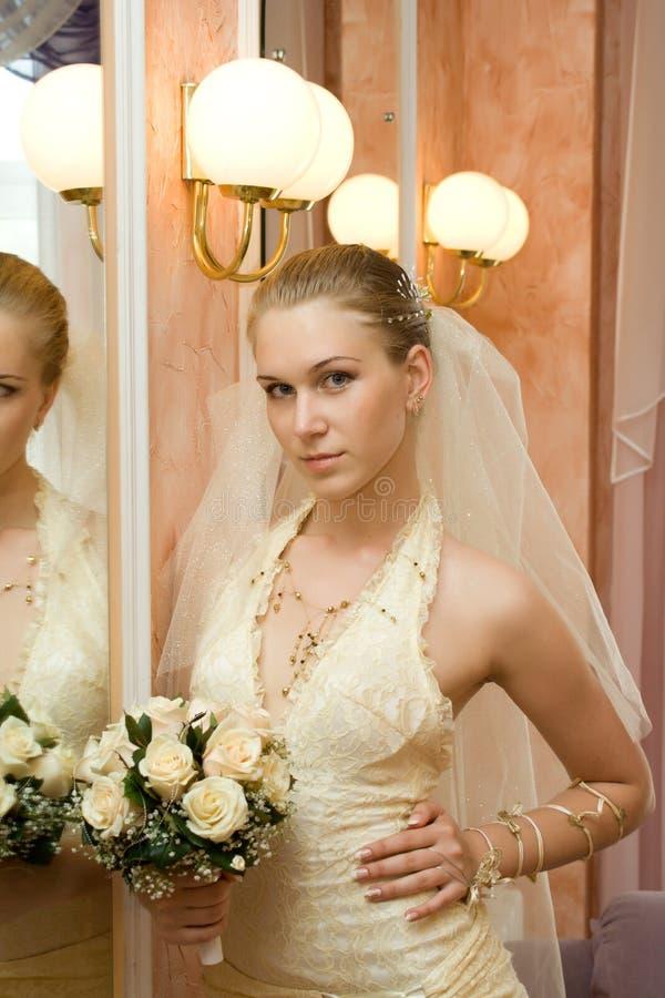 Die Braut nahe einem Spiegel lizenzfreie stockfotografie