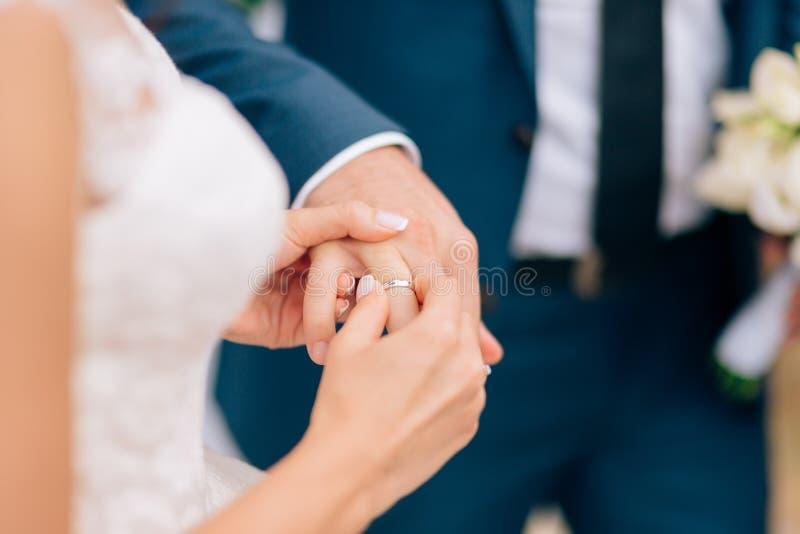 Die Braut setzt den Ring auf den Bräutigam am Hochzeit ceremon lizenzfreies stockbild