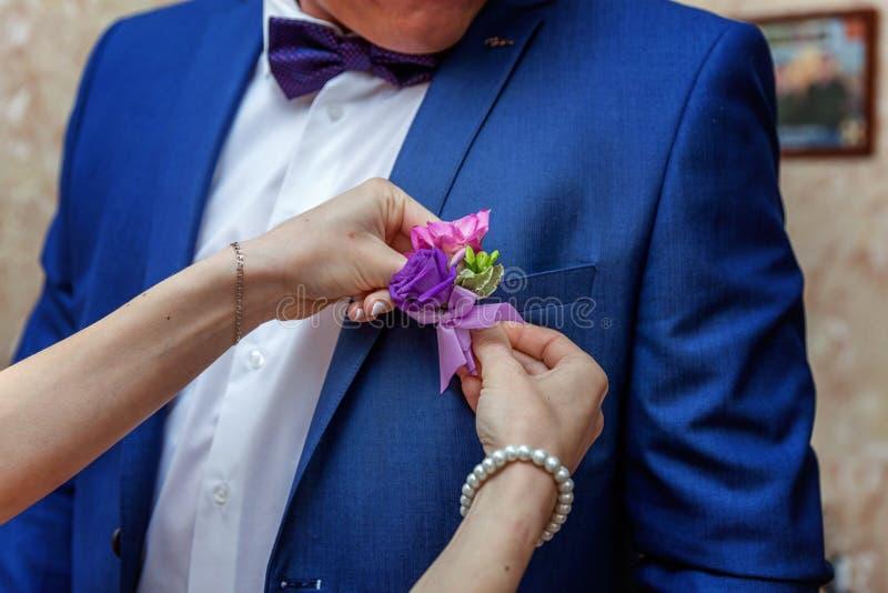 Die Braut trägt einen Bräutigam Boutonniere lizenzfreie stockbilder