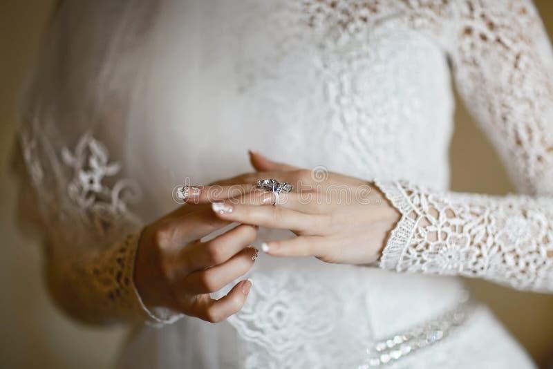 Die Braut trägt einen Ring mit einem Kiesel, eine schöne Maniküre in den Händen der Braut, Spitzekleid, Morgen der Braut stockfotos