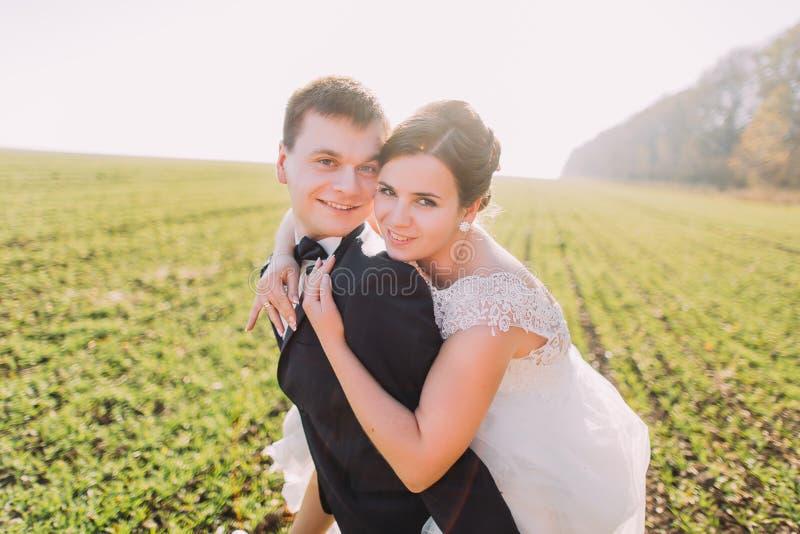 Die Braut umarmt den Bräutigam zurück auf dem grünen Gebiet lizenzfreie stockbilder