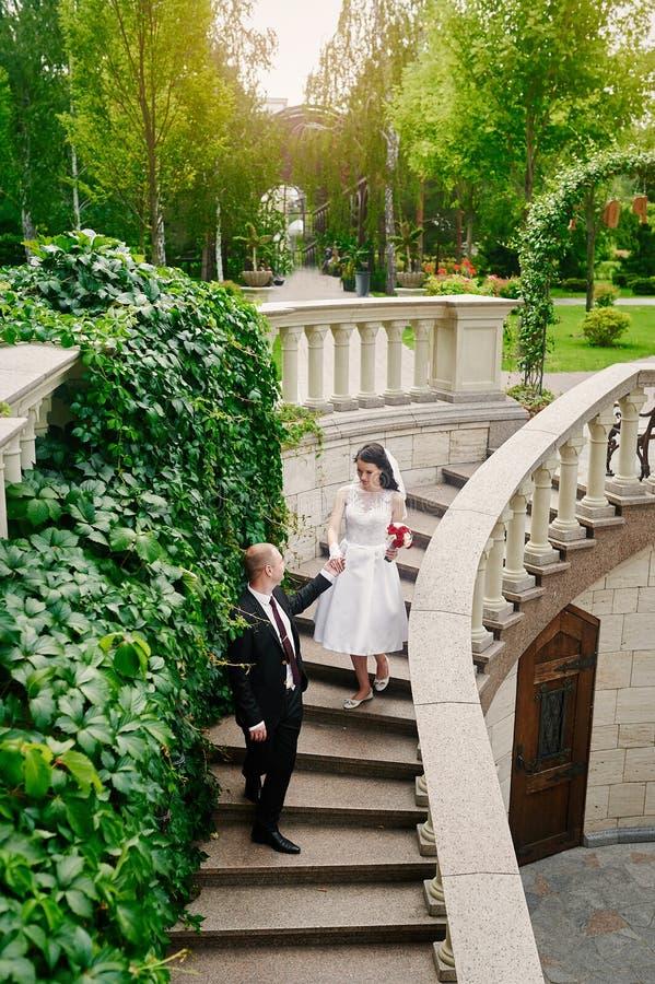 Die Braut und Bräutigam, die in Sommer gehen, parken draußen mit Architektur stockbilder