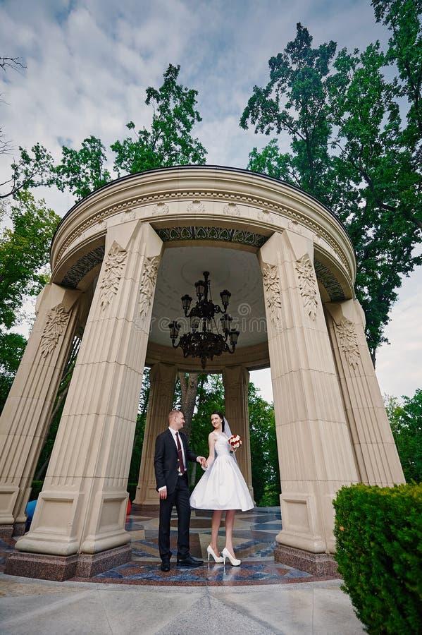 Die Braut und Bräutigam, die in Sommer gehen, parken draußen mit Architektur lizenzfreie stockfotografie