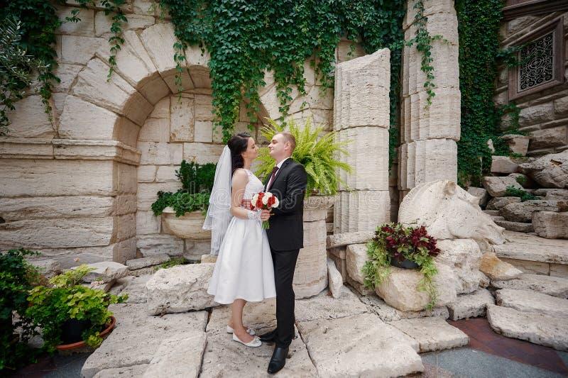 Die Braut und Bräutigam, die in Sommer gehen, parken draußen mit Architektur lizenzfreie stockfotos