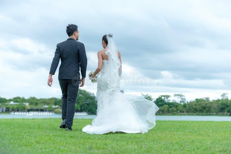 Die Braut- und Bräutigampaare in Heiratskleidung mit einem Blumenstrauß von Blumen in den Händen gegen den Hintergrund stockbild