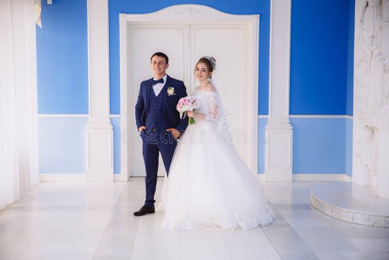 Die Braut und der Bräutigam bereiten vor sich, die Trauung durch den Arm einzutragen Sie lächeln und genießen den Hochzeitstag he lizenzfreie stockfotos