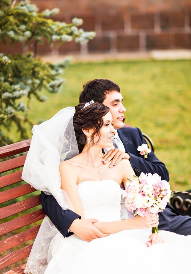 Die Braut und der Bräutigam, die auf einer Bank im Park sitzen lizenzfreie stockfotografie