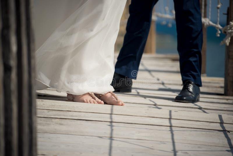 Die Braut und der Bräutigam führen ihre Schuhe auf dem Pier an diesem heraus vor stockfoto