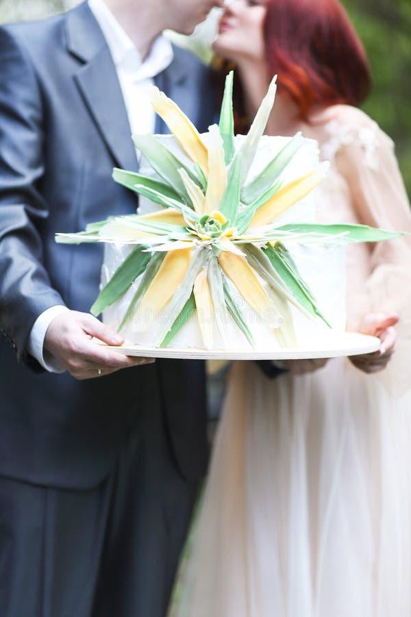 die Braut und der Bräutigam mit Kuchen an der Hochzeit Fokus auf dem Kuchen lizenzfreie stockbilder
